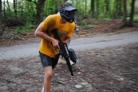 A boy with his gun playing paintball in the forest